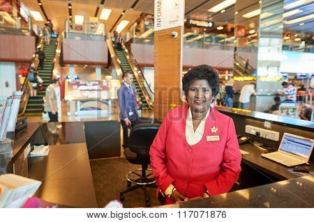 SINGAPORE - NOVEMBER 04, 2015: help desk staff at Changi Airport. Singapore Changi Airport, is the primary civilian airport for Singapore, and one of the largest transportation hubs in Southeast Asia