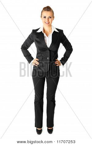 Full length portrait of smiling modern business woman with hands on hips