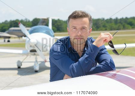 Man leaning on aircraft holding sunglasses