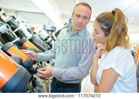 Man and young lady looking at telescopes