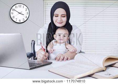 Mom Working While Holds Her Baby