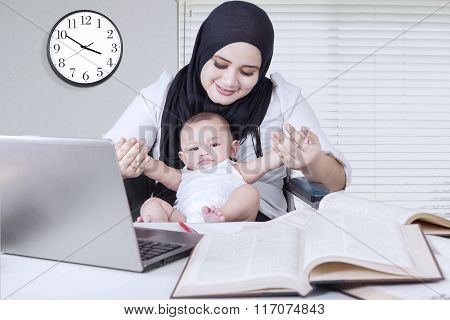 Mother Playing With Baby While Working