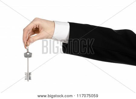 Business Theme: Real Estate Agent In The Jacket In His Hand The Key To A New Apartment On The White