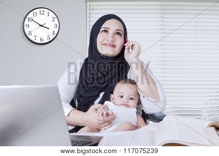 Thoughtful Mom Working While Carrying Baby