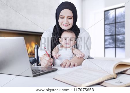 Woman Working While Carrying Her Baby
