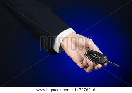 Business And Gift Theme: Car Salesman In A Black Suit Holds The Keys To A New Car On A Dark Blue Bac