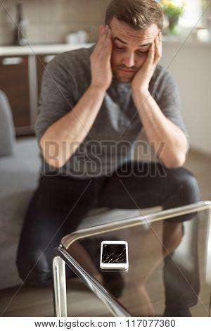 Worried Man Looking At Broken Smart Phone