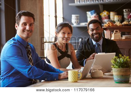 Portrait Of Three Businesspeople Working At Laptop In Cafe