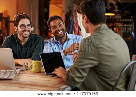 Three Male Fashion Designers In Meeting Using Laptop