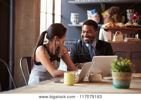 Two Businesspeople Working At Laptop In cafe