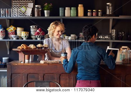 Customer In Coffee Shop Ordering Using Digital Tablet