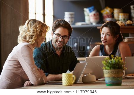 Three Businesspeople Working At Laptop In cafe