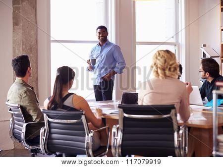 Businessman Addressing Team Meeting Around Table
