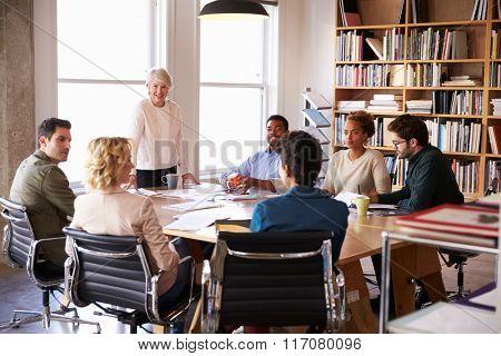 Senior Businesswoman Addressing Team Meeting Around Table