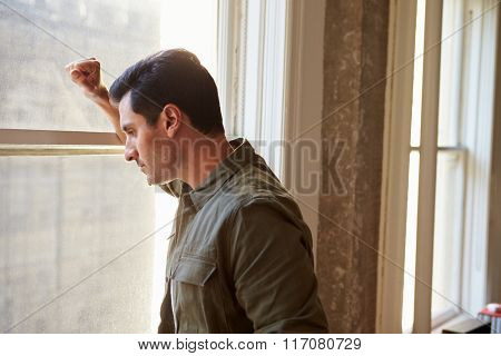 Casually Dressed Businessman Looking Out Of Office Window