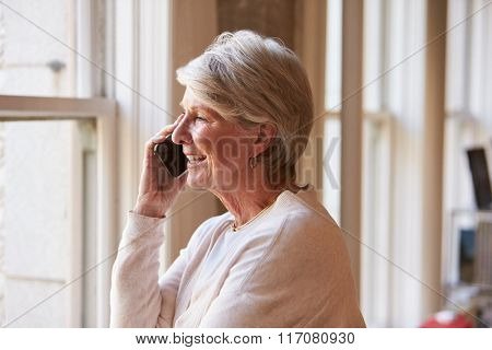 Senior Businesswoman On Mobile Phone In Office