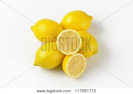 whole and halved ripe lemons on white background