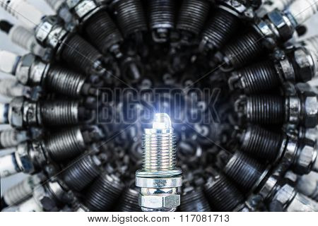 New spark plug on a background of old spark plugs