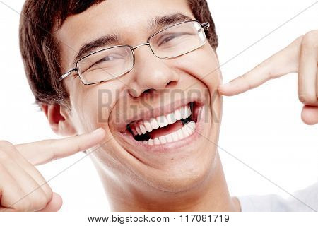 Face close up of young hispanic man wearing glasses pointing with forefingers at his toothy smile with perfect healthy white teeth isolated on white background - dental care concept