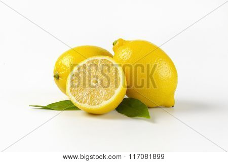 two and half lemons with leaves on white background