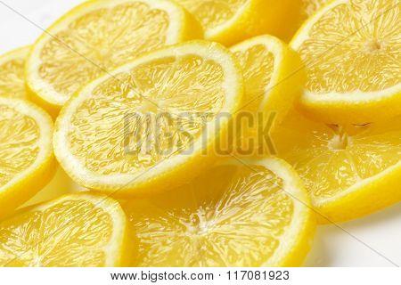 heap of fresh lemon slices on white
