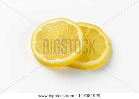 two thin slices of fresh lemon on white background