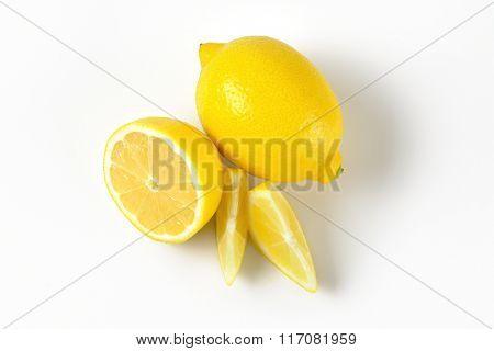 whole and sliced juicy lemons on white background