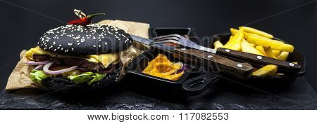 Black burger. Set of the black burger. Stone plate with: black burger roll slices of juicy marble beef,fusedcheese,fresh salad with French fries on a cast-iron griddle, with chili sauce and guakomole.