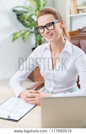 Pleasant office worker sitting at the table
