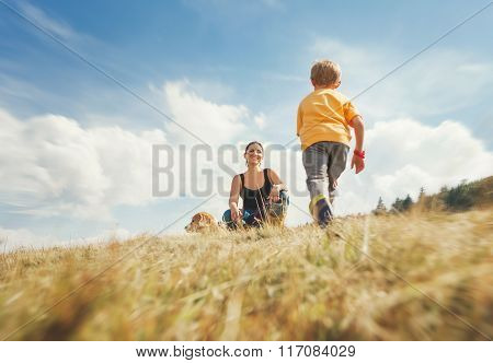 Happy Mother And Son Walk On The Golden Field With Dog