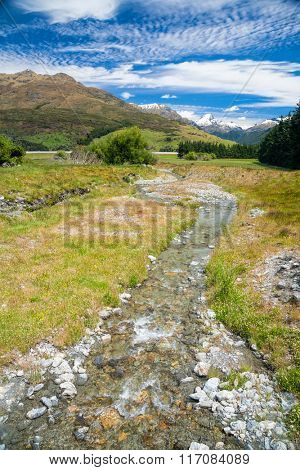 New Zealand's landscape with small stream or brook in foreground and snow capped mountains in background on a sunny summer day