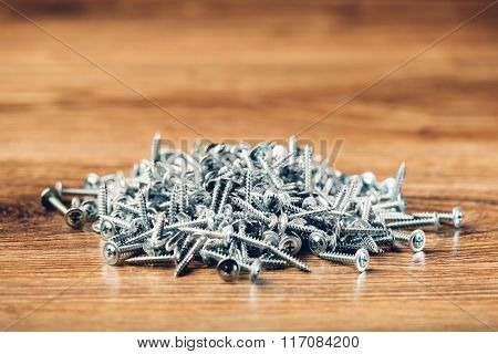 screws fasteners hardware heap on wooden background