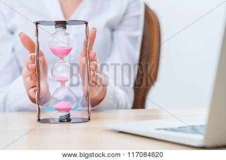 Pleasant woman holding sandglass