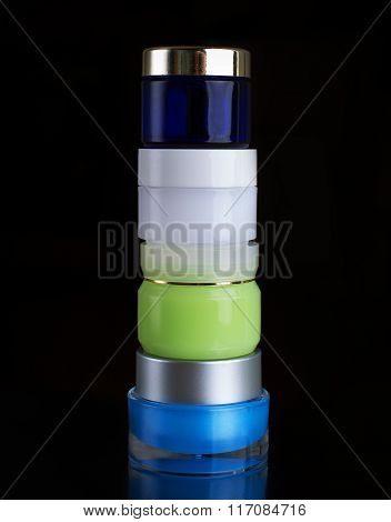 Stack Of Various Spa Cosmetics Isolated On Black Background.