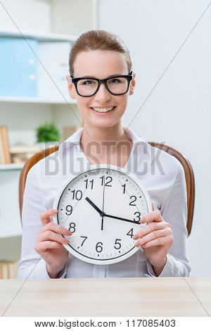 Smiling woman holding clock