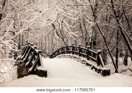 Beautiful old stone bridge of  winter forest in the snow at sunset frosty days. Trees covered in fro