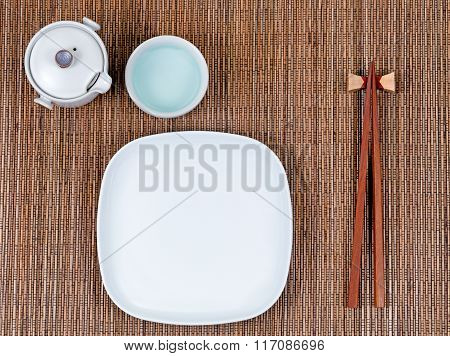 Bamboo Mat With Traditional Asian Utensils Plus White Dinner Plate And Tea