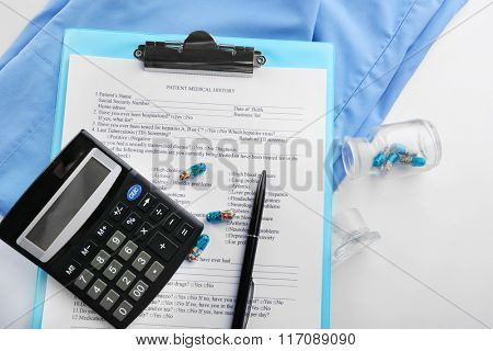 A stethoscope, coat, calculator and clipboard, close-up