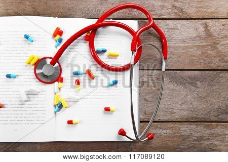 Stethoscope  and colourful pills on a book, close up