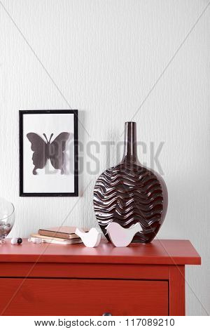 Room interior with red wooden commode, vase and frame on light wall background