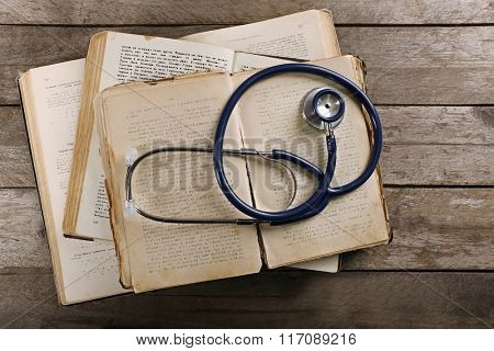 Book and stethoscope on wooden table, top view