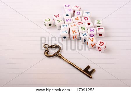 A Beautiful Metal Key And Colurful Cube Letters