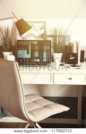Workplace with table, lamp and laptop in living room