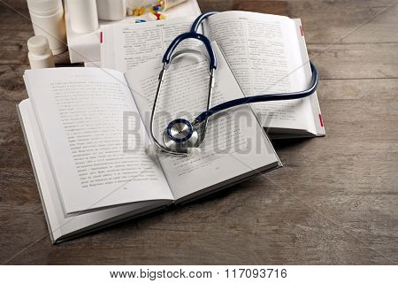Books, bottles of pills and stethoscope on wooden table closeup