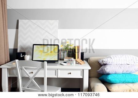Workplace with table and laptop in living room