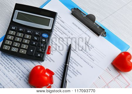 A stethoscope, pen, calculator and clipboard, close-up