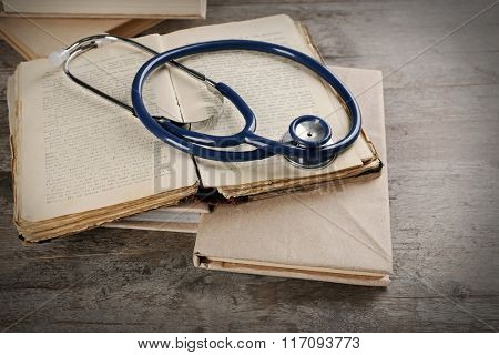 Books and stethoscope on wooden table closeup