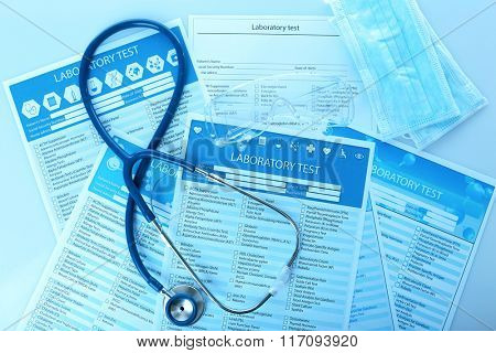 Stethoscope, medical mask and laboratory test lists, close up
