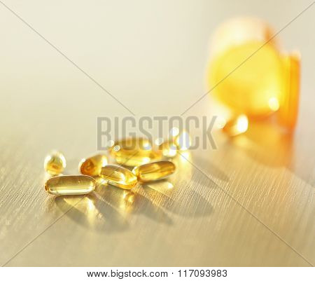 Capsules spilled from yellow pill bottle on wooden table, close up