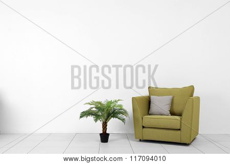 Living room interior with green armchair and plant on white wall background